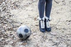在足球附近的女孩的脚 与球的街道比赛 免版税库存图片