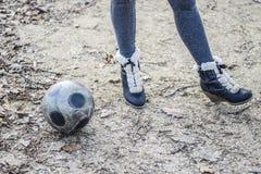 在足球附近的女孩的脚 与球的街道比赛 免版税库存照片