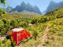在足迹旁边的红色野营的帐篷在山 免版税库存照片