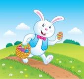 在足迹的兔宝宝与复活节篮子用鸡蛋 免版税库存照片