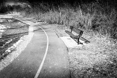 在足迹附近的一条空的长凳 免版税库存图片