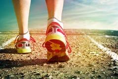 在跑在沥青的运动鞋人的脚 免版税库存图片