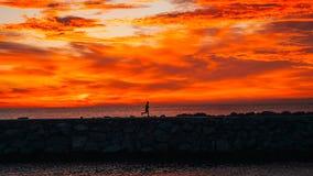 在跑在海旁边的日出的赛跑者 免版税库存图片