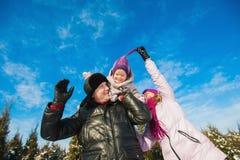 在跑明亮的衣裳冬天的乐趣的年轻美丽的家庭跳跃和,雪,生活方式,寒假 库存照片