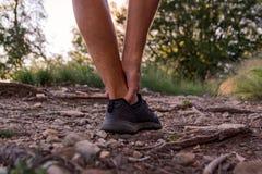 在跑步期间的男性踝关节损伤 库存照片