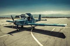 在跑道的一架小飞机以mounta为背景 图库摄影