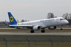 在跑道的乌克兰国际航空公司巴西航空工业公司ERJ190-100航行器着陆 免版税库存图片