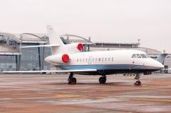在跑道的停放的私有飞机在机场终端附近 白色民事,现代喷气机 库存图片