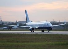 在跑道的大白色喷气式客机飞机在机场 免版税库存照片