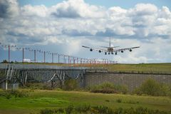 在跑道的重的货物飞机着陆有豪华的绿色和蓝天的 库存图片