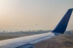 在跑道的飞机翼在日出的本古理安机场 免版税库存图片