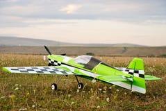 在跑道的RC式样绿色飞机 库存照片