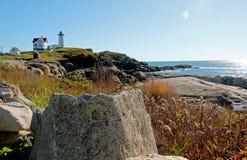 在距离的灯塔在岩石岸 免版税库存图片