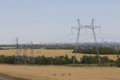 在距离高层建筑物的输电线 免版税库存照片