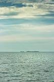 在距离的货船在海岛附近 免版税图库摄影