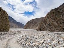 在距离走和骑自行车在S形曲线的人通过岩石山谷塑造了轨道 免版税图库摄影