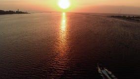在跟踪小船船之后-空中与很少云彩和温暖的黄昏的灯塔史诗电影射击-寄生虫视图 影视素材