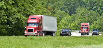 在跨境的两辆半红色卡车 免版税库存照片