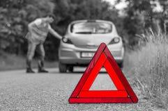 在路和不快乐的司机的残破的汽车与红色三角 库存图片