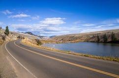 在路和小山之间的平静的湖 免版税库存图片