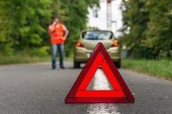 在路和警告三角的残破的汽车 免版税库存照片
