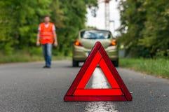 在路和警告三角的残破的汽车 库存图片