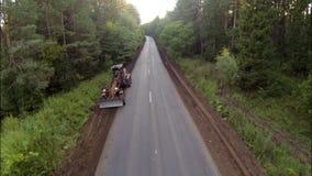 在路在森林,鸟瞰图的平地机 股票视频