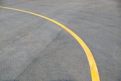 在路地板纹理和背景的黄色曲线交通线 库存照片