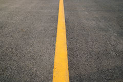 在路地板纹理和背景的Erspective黄色平直的交通线 免版税库存照片