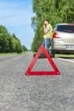 在路旁、司机与电话和残破的汽车的紧急标志 免版税图库摄影