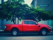 在路旁边停放的一辆红色卡车 免版税库存照片