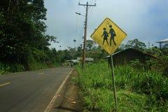 在路旁边的标志在告诉一个小的村庄有学校和孩子提出 免版税图库摄影