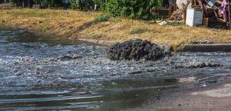 在路污水舱口盖外面的水流量 污水排水设备喷泉  下水道系统事故  肮脏的污水水流量喷泉 库存照片