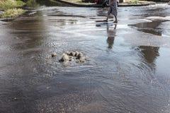 在路污水舱口盖外面的水流量 污水排水设备喷泉  下水道系统事故  肮脏的污水水流量喷泉 免版税库存照片