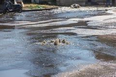 在路污水舱口盖外面的水流量 污水排水设备喷泉  下水道系统事故  肮脏的污水水流量喷泉 免版税图库摄影