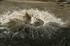 在路污水舱口盖外面的水流量 污水排水设备喷泉  下水道系统事故  肮脏的污水水流量喷泉 免版税库存图片