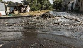 在路污水舱口盖外面的水流量 污水排水设备喷泉  下水道系统事故  肮脏的污水水流量喷泉 图库摄影