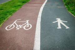 在路沥青绘的自行车和步行者标志 图库摄影