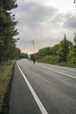 在路的一辆人骑马自行车 免版税图库摄影