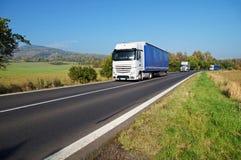 在路的三辆白色卡车在乡下 免版税库存图片