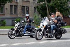 在路的两个骑自行车的人骑马 免版税库存图片