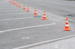 在路的交通锥体 与白色标记和交通锥体的闭合的汽车停车场在街道上使用了在路的警报信号 免版税库存图片
