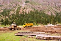 在路的卡车在洪水以后的修理期间在中亚之间山的一个谷  免版税库存图片
