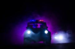 在路的夜加速警车照明设备  在移动与雾的路的警车 选择聚焦 追逐 免版税库存照片
