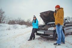 在路的夫妇有残破的汽车的 免版税库存照片