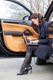 在路的工作 一件黑暗的外套的妇女有膝上型计算机的 免版税库存照片