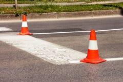 在路的工作 中央锥体锥体建筑重点 交易锥体,与在沥青的白色和橙色条纹 街道和交通标志发信号的 库存照片