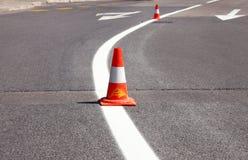 在路的工作 中央锥体锥体建筑重点 交易锥体,与在沥青的白色和橙色条纹 街道和交通标志发信号的 库存图片