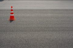 在路的工作 建筑锥体 交通锥体,与在沥青的白色和橙色条纹 街道和交通标志发信号的 免版税库存照片