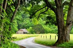 在路的弯曲处的一栋小的原木小屋。 库存照片